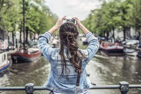 Netherlands, Amsterdam, female tourist taking a selfie with smartphone - RIBF000090