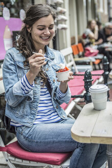 Netherlands, Amsterdam, female tourist sitting in a street cafe eating frozen yogurt - RIBF000091