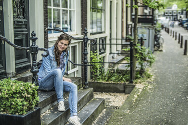Netherlands, Amsterdam, smiling woman sitting on steps in front of house - RIBF000113