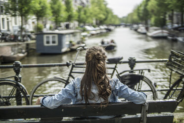 Netherlands, Amsterdam, woman ralxing on a bench in front of town canal - RIBF000098