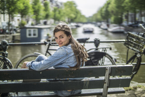 Netherlands, Amsterdam, smiling woman sitting on a bench in front of town canal - RIBF000099