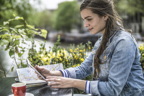 Netherlands, Amsterdam, woman sitting in a street cafe using digital tablet - RIBF000103