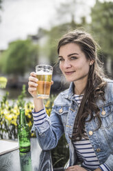 Netherlands, Amsterdam, Portrait of woman drinking glass of beer in a street cafe - RIBF000105