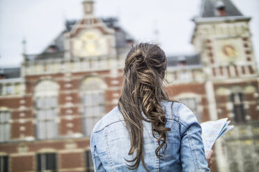 Netherlands, Amsterdam, back view of woman with city map in front of central station - RIBF000109