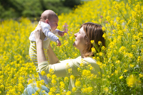 Mother with her baby girl on yellow blossoming field of flowers - WWF003899