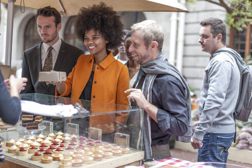 Woman buying pastries at food stall at city market - ZEF006583