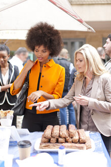 Women choosing food from stall at city market - ZE007019
