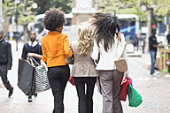 Back view of three women side by side on shopping tour - ZE006599