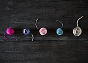 Row of five different balls of wool on black wood - PDF000962