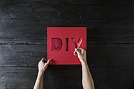 Man's hands cutting out letters of red cardboard - PDF000959
