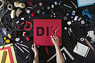 Man's hands cutting out the word DIY of red cardboard - PDF000956