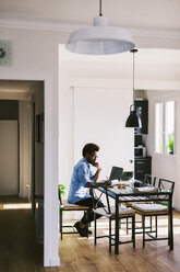 Young man working with laptop at home office - EBSF000636