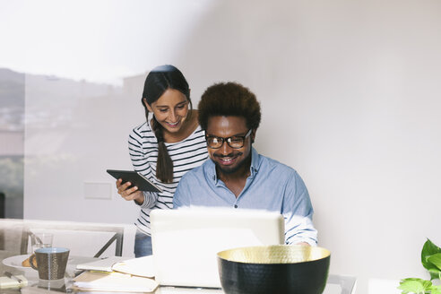 Young man and woman working with laptop and digital tablet at home office - EBSF000648
