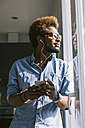 Young man listening to music from smartphone looking out of the window - EBSF000655