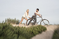 Young couple with bicycle on a beach dune - ZEF005289