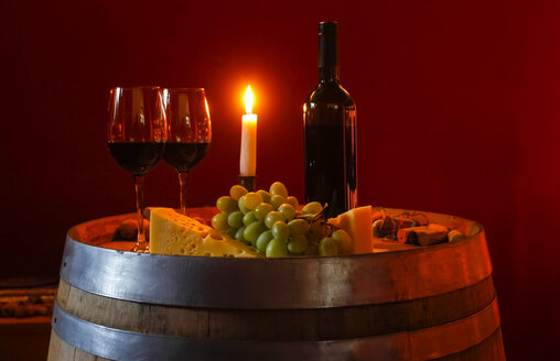 Two glasses of red wine, bottle, grapes, cheese and lighted candle on a wine cask in a wine cellar - JTF000665