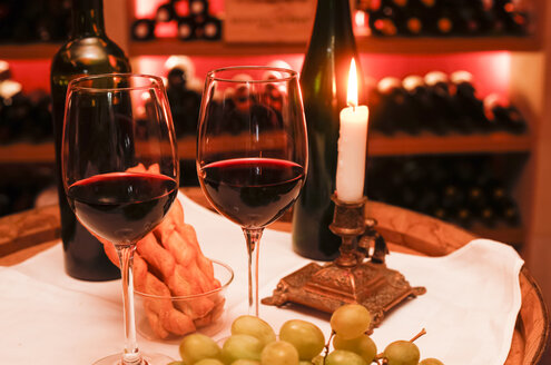 Two glasses of red wine, grapes, cheese sticks and lighted candle in a wine cellar - JTF000666