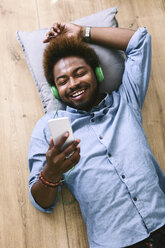Young Afro American man lying on floor with headphones and smart phone - EBSF000612