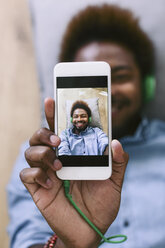 Young Afro American man lying on floor, taking selfie - EBSF000615