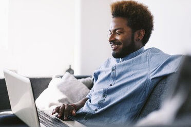 Young Afro American man sitting on couch, using laptop - EBSF000620