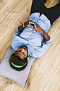 Young Afro American man lying on floor with headphones and smart phone - EBSF000629