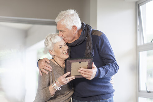 Senior couple with picture frame at home - ZEF005516