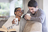 Young couple with coffee cups at home - ZEF005539