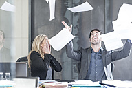 Businessman throwing papers in the air, woman looking shocked - ZEF005609