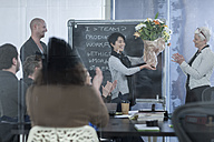 Businesswoman receiving bunch of flowers on a casual meeting - ZEF005629