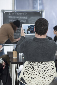 Casual businessman taking picture with digital tablet on a meeting - ZEF005673