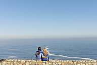 South Africa, two women sitting arm in arm on a wall at the coast - ZEF005636
