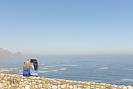 South Africa, two women sittin on a wall at the coast taking a picture with digital tablet - ZEF005637