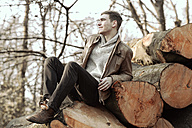 Young man sitting on stack of tree trunks - GDF000734