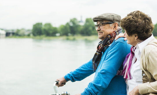 Senior couple with bicycle in front of water - UUF004497