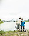 Back view of senior couple standing at water's edge with walking stick and wheeled walker - UUF004512