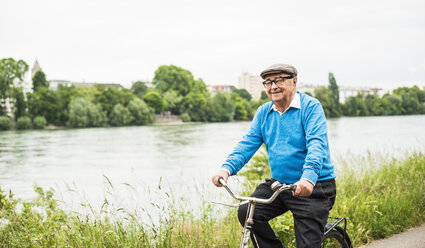 Smiling senior man riding bicycle - UUF004540