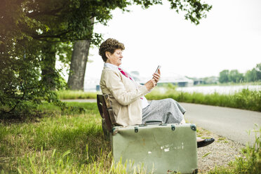 Senior woman sitting on bench using phablet - UUF004565