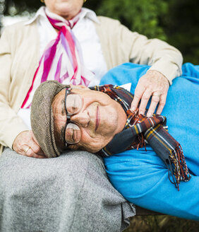 Portrait of senior man lying with head on his wife's lap - UUF004547