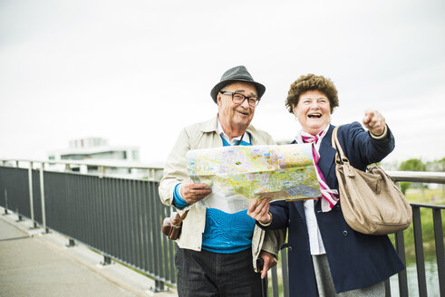 Senior couple with map standing on a bridge - UUF004551