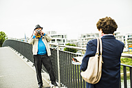 Senior man taking a picture of his wife - UUF004553