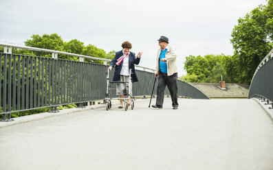 Senior couple with walking stick and wheeled walker on a bridge - UUF004555