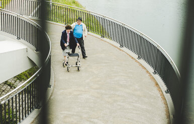 Senior couple with walking stick and wheeled walker on a bridge - UUF004558
