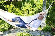Businessman relaxing in hammock in a garden - MAEF010632