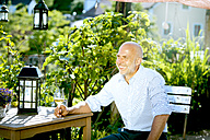 Portrait of happy man sitting with glass of white wine relaxing in the garden - MAEF010641