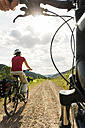 Couple riding bicycle at countryside - UUF004570