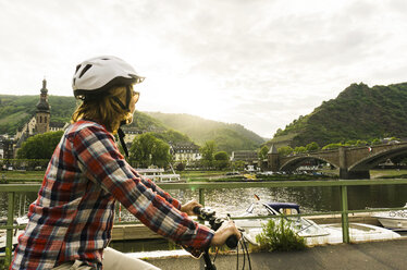 Germany, Cochem, woman riding bicycle along Moselle - UUF004572