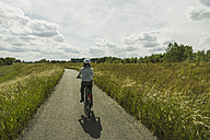 Woman riding bicycle at countryside - UUF004581