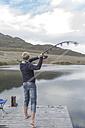 Young man fishing at a lake - ZEF005782