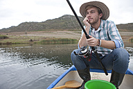 Fishing man sitting in a canoe on a lake - ZEF005795