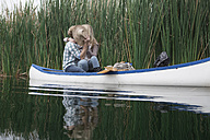 Young couple kissing in a canoe on a lake hiding behind straw hat - ZEF005797